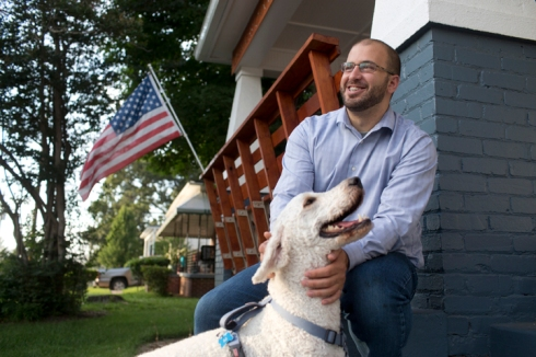Farris Barakat with his dog on the front porch of The Light House Project.